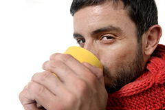 Attractive man drinking cup of coffee tea in winter warming his hands Royalty Free Stock Photography