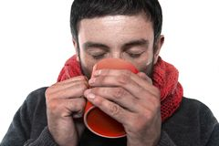 Attractive man drinking cup of coffee tea in winter warming his hands Stock Images
