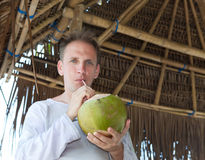 Attractive man drinks coconut juice from a nut Royalty Free Stock Photos