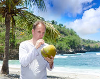 Attractive man drinks coconut juice from a nut on a beach at the sea Royalty Free Stock Photo