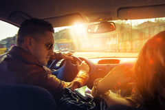 Attractive man driving car and look at his girl Royalty Free Stock Photography