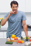 Attractive man eating a slice of bell pepper Stock Photo