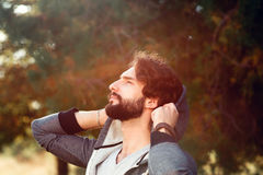 Attractive man enjoying sun warm, close-up. Portrait of young bearded guy, having sunbath in forest. Nature, spring, relax, pleasure concept Royalty Free Stock Image