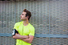 Attractive man enjoys a wonderful morning after intense fitness training while listen to music in headphones Stock Photos