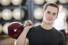 Attractive Man Exercising With Kettlebell In Gym Stock Photos