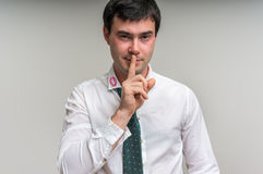 Attractive man with finger on lips and lipstick on shirt collar. Attractive man with finger on lips and red lipstick on shirt collar making silence gesture Stock Photo