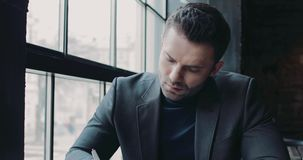 Attractive man in a formal black suit putting a signature on the documents, then looks right towards the camera. Office
