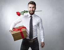 Attractive man with gift package. And rose in his mouth Stock Image