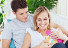 Attractive man giving a present to his girlfriend. Lying on the couch at home Royalty Free Stock Image