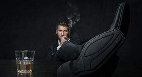Attractive man with a glass of whiskey and a cigar. His feet he put up on the desktop Stock Photos