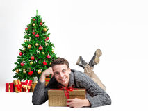 Attractive man with a golden present is lying on the floor in front of a christmas tree.  Royalty Free Stock Photos