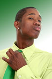 Attractive Man In Green Adjusting Necktie Over Green Background Stock Images