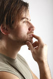 Attractive man with green shirt looks thoughtful Stock Images