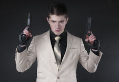 Attractive man with a gun wearing a white suit Stock Photography