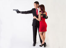 Attractive Man With Guns and Sexy Woman. An image of a young men holding two guns being embraced by a young women in a tight dress Stock Photos