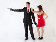 Attractive Man With Guns and Sexy Woman. An image of a young men holding two guns being embraced by a young women in a tight dress Stock Photo