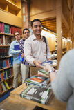 Attractive man handing a book to the female librarian. Attractive men handing a book to the female librarian in library Stock Images