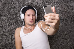 Attractive man with headphones unhappy to make selfie with his m Stock Photo