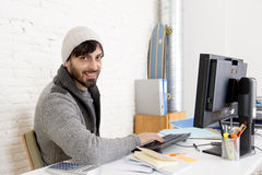 Attractive man in hipster beanie  businessman working happy at office with computer Stock Photography