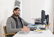 Attractive man in hipster beanie  businessman working happy at office with computer Stock Photo