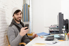 Attractive man in hipster beanie and trendy style businessman working happy at home office with desktop computer Stock Photos