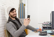 Attractive man in hipster beanie and trendy style businessman working happy at home office with desktop computer Royalty Free Stock Photos