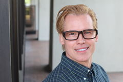Attractive man with his hair colored blond and a perfect smile wearing glasses Royalty Free Stock Photos