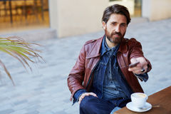 Attractive man hold out waiter a bank card. Portrait of fashionable handsome man paying for his coffee with a credit card at the cafe, customer paying at a stock image