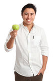 Attractive man holding apple wearing a white shirt Royalty Free Stock Photos