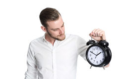 Attractive man holding a clock. An attractive man wearing a white shirt holding a big clock, standing against a white background Royalty Free Stock Photography