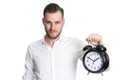 Attractive man holding a clock. An attractive man wearing a white shirt holding a big clock, standing against a white background Royalty Free Stock Images
