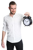 Attractive man holding a clock. An attractive man wearing a white shirt holding a big clock, standing against a white background Stock Photography