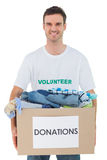 Attractive man holding donation box with clothes Royalty Free Stock Photo
