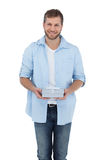 Attractive man holding a gift looking at camera Stock Photos