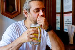 Attractive man in casual clothes is drinking beer while sitting at bar counter in pub. Attractive man holding an half-pint of beer in casual clothes is drinking stock photography