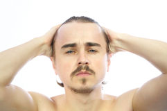 Attractive man holding his head Royalty Free Stock Image