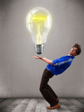 Attractive man holding realistic 3d light bulb Royalty Free Stock Photo