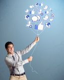 Attractive man holding social icon balloon. Attractive young man holding social icon balloon Stock Images