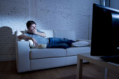 Attractive man at home lying on couch at living room watching tv  eating popcorn bowl looking surprised Stock Images