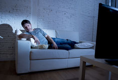 Attractive man at home lying on couch at living room watching tv eating popcorn bowl looking surprised Royalty Free Stock Photo