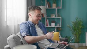 Attractive Man at Home Sitting on Sofa Does Video Call Using Laptop Computer.  stock footage