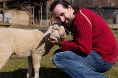 Attractive man hugging a cute lamb Stock Images