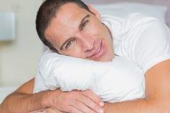 Attractive man hugging his pillow Royalty Free Stock Photos