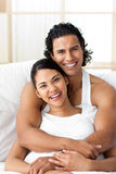 Attractive man hugging his wife lying on the bed Stock Photo