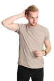 Attractive man isolated on white background. One man standing wearing a beige tshirt, standing in front of a white background looking at camera Stock Images