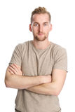 Attractive man isolated on white background. One man standing wearing a beige tshirt, standing in front of a white background looking at camera Royalty Free Stock Images