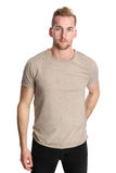 Attractive man isolated on white background. One man standing wearing a beige tshirt, standing in front of a white background looking at camera Stock Photo