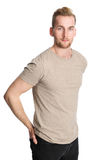 Attractive man isolated on white background. One man standing wearing a beige tshirt, standing in front of a white background looking at camera Royalty Free Stock Photo