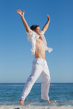 Attractive man jumping on beach Royalty Free Stock Photo