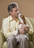 Attractive man kissing dog. Stock Photo